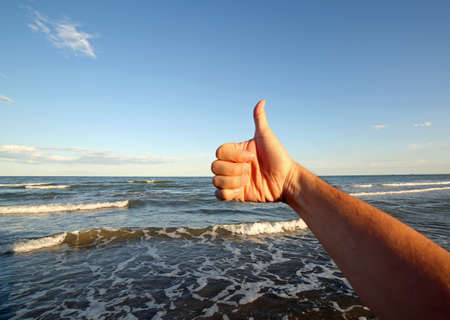 thumb up to make ok towards the crystal clear and bubbling sea