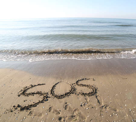 big text SOS on the sand of the beach Stock Photo