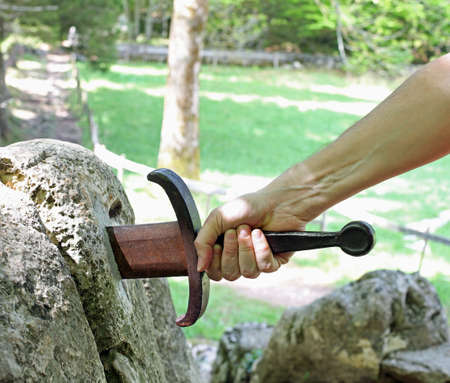 Hand and the legendary Excalibur sword in the stone