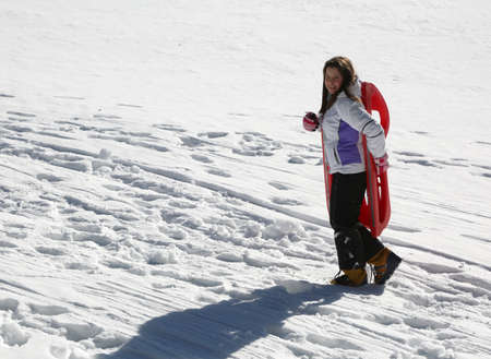 little girl brings the sledge by hand up a hill with snow