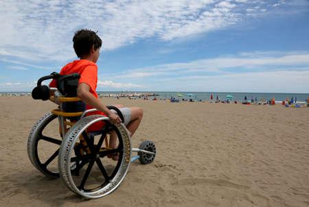 hoffnungsvoller Junge schaut vom Rollstuhl am Strand auf das Meer