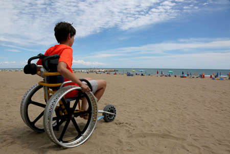 hopeful boy looks at the sea from the wheelchair at the beach Фото со стока - 101154793