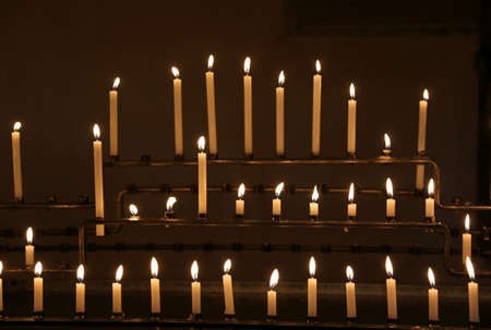 many candles with flames during religion mass in the church Stock Photo
