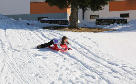 little girl play in winter with red plastic sled Banco de Imagens