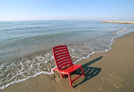 Red abandoned chair is bathed by the waves of the sea
