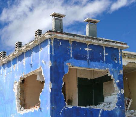 big hole into the blue wall of a destroyed house