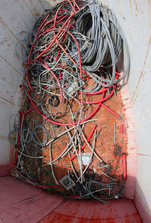 broken colored electric wires in a garbage container