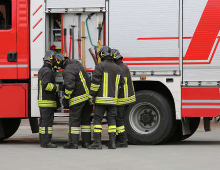 firefighters sort the water pipes near the fire truck 写真素材