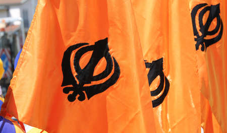 many orange flags with khanda symbol of sikhism Stock Photo