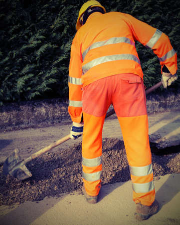 man at work with high visibility clothing in the construction site with vintage effect