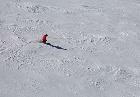 One skier in the slope with snow with red clothing