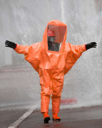 Person with orange protective suit against chemical and bacteriological virus attacks Stock Photo
