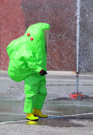 Person with a green protective suit against chemical and bacteriological agents