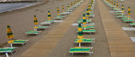 beach full of umbrellas with deck chairs both closed by the empty sea