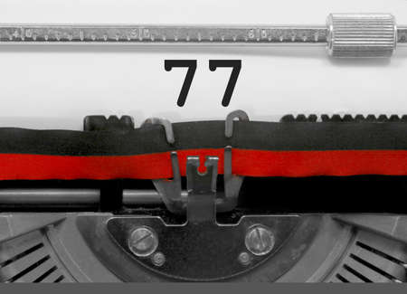 77 Number text written by an old typewriter on white sheet