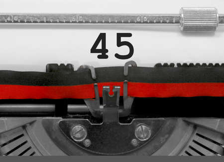 45 Number text written by an old typewriter on white sheet Фото со стока