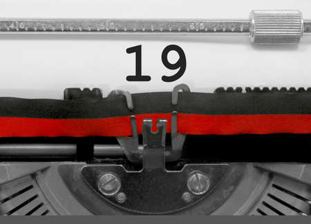 19 Number text written by an old typewriter on white sheet Stock Photo