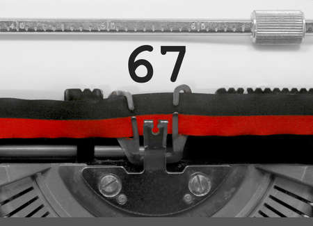67 Number text written by an old typewriter on white sheet Stock Photo