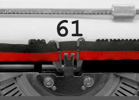 61 Number text written by an old typewriter on white sheet Stock Photo