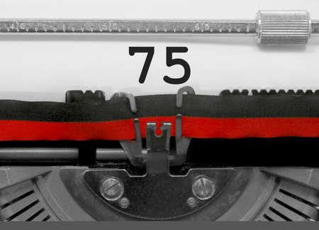 75 Number text written by an old typewriter on white sheet Stock Photo