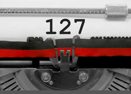 127 Number text written by an old typewriter on white sheet
