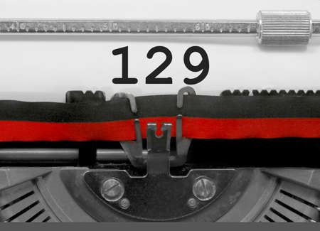 129 Number text written by an old typewriter on white sheet Stock Photo