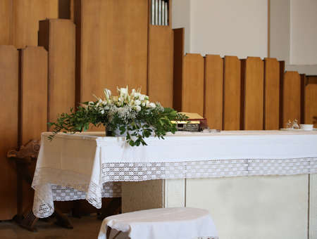potted flowers on the altar in the church during the noly mass