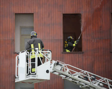 firefighter on a ladder to reach the top floors of a building and extinguish a fire Stock Photo