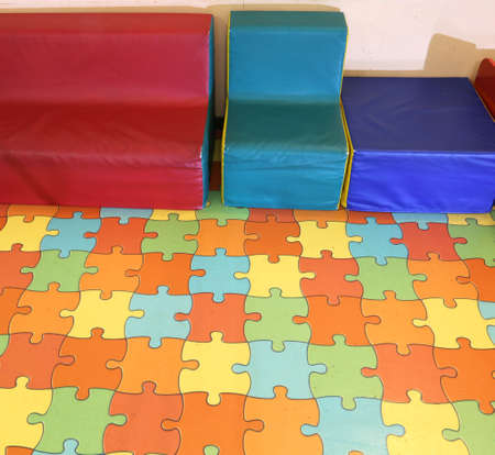 small armchairs for children with a colorful puzzle mat in a kindergarten
