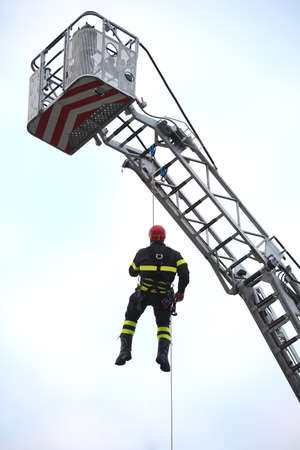 fireman on action hanging on the platform Imagens