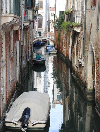 Many houses near the narrow water way and many boats in Venice Italy Stock Photo