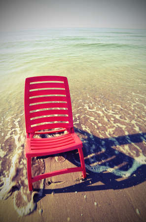red plastic deckchairs on the sea shore with vintage effect