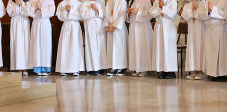 many young people at first communion in the church during the holy mass Stock Photo