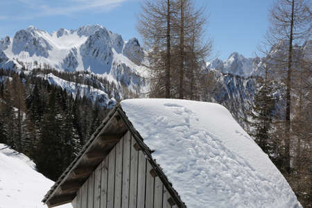 landscape with withe mountains and the roof of a hut in winter