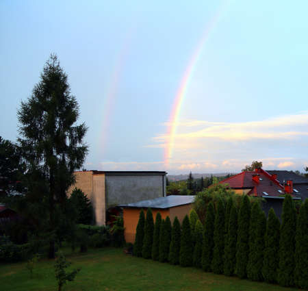rare double rainbow above the city after a heavy summer storm