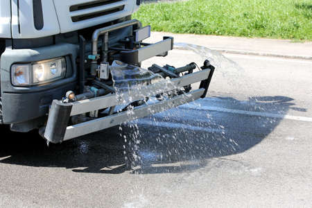 Roadwashing truck with splashes of water to wash the asphalt Stock Photo