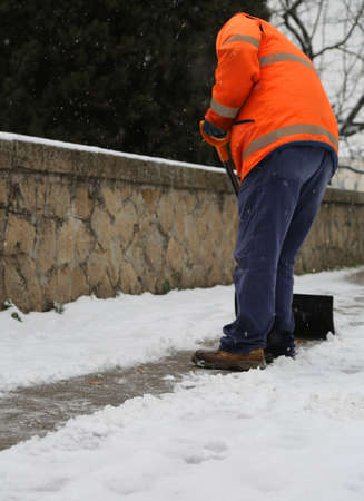 Snow spreader shovels the sidewalks after the snowfall Stockfoto