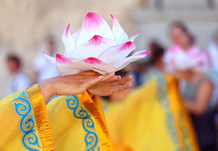 hand holds a blossomed lotus flower