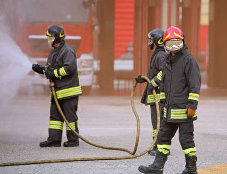 three firemen with the mask extinguish a fire with white foam