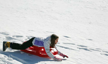 little girl descends lying on a sled sliding on the soft white snow Standard-Bild
