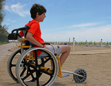 boy the horizon from the wheelchair stops in the empty beach Stock Photo - 103362983