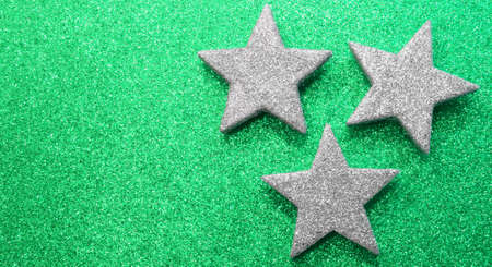 three large silver stars on green glittery background