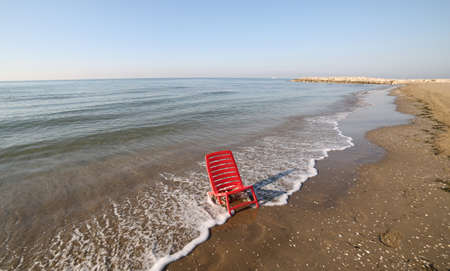 red small deckchair to relax by the sea in summer without any person