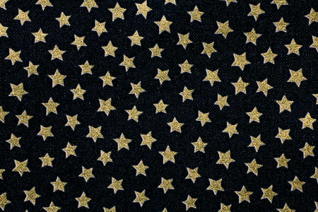Black fabric with the background of many five-pointed stars Фото со стока