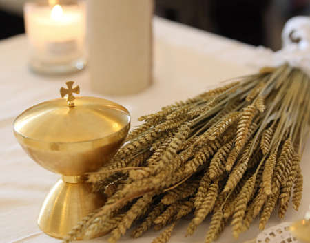 golden calyx and the ears of wheat over an altar in church and a candles
