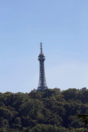 tip of the Petrin Tower in Prague similar to the Eiffel Tower that appears in the trees of the forest Redakční