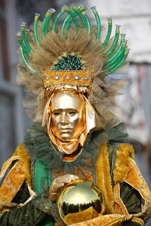 Venice, Italy - February 5, 2018: golden Mask near the Ancient bridge of sighs during Carnival Festival