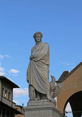 Florence, Italy - August 21, 2015: Old Statue of Dante Aligheri a famous italian poet and writer in the square and blue sky on background. Only editorial Use