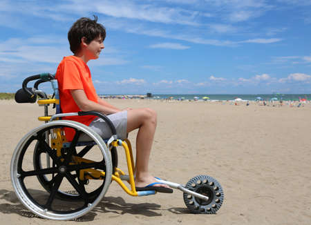 boy looks at the sea from the beach because he is in a wheelchair