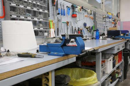 Interior de un taller mecánico para la reparación de bicicletas y un gran tornillo de banco azul en el banco de trabajo con muchas herramientas e implementos